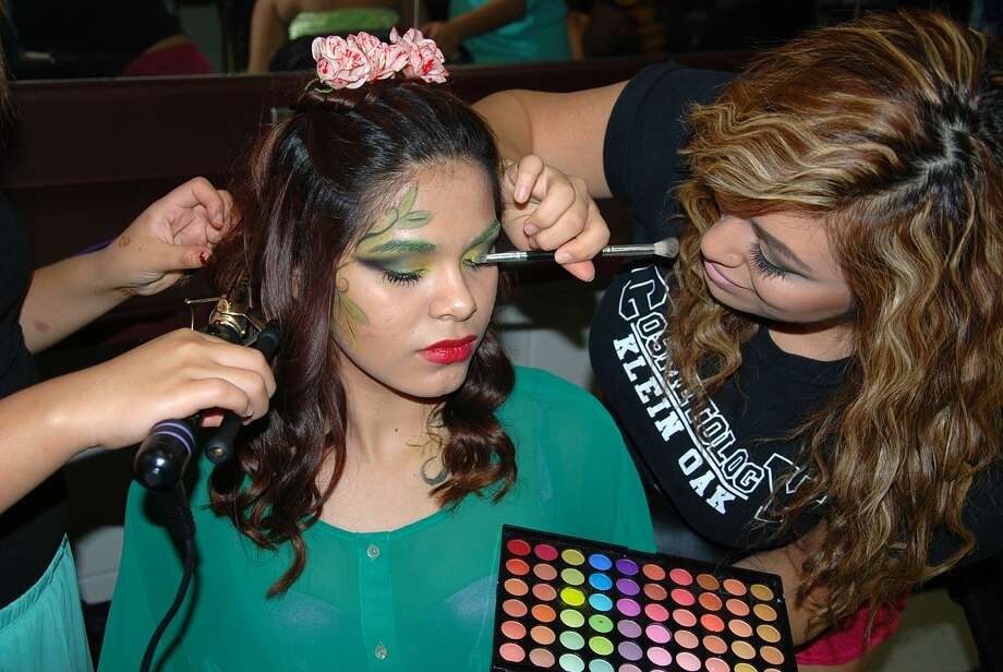 Jersey Village High School student Alexis Cabrera puts decorative makeup around the eyes of Cypress Falls High School student Marisol Cardenas prior to a cosmetology fashion show at Langham Creek High School. Cardenas was a model for the class. Photo: Courtesy
