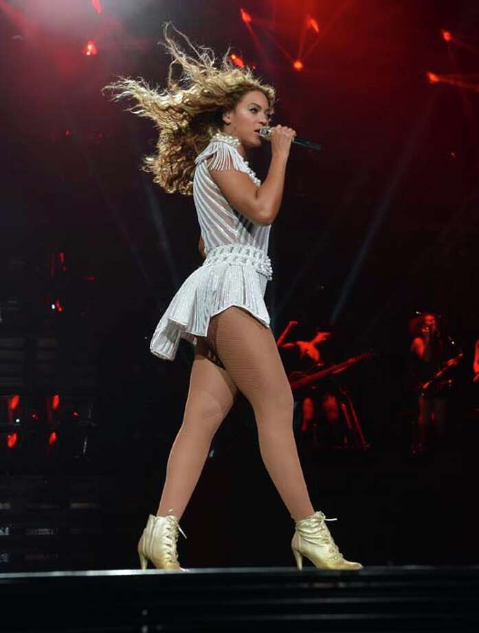 "HOUSTON, TX - JULY 15:  Entertainer Beyonce performs on stage during ""The Mrs. Carter Show World Tour"" at the Toyota Center on July 15, 2013 in Houston, Texas. Beyonce wears a custom hand beaded white peplum one piece by Ralph & Russo, Stuart Weitzman shoes and hosiery by Capezio. (Photo by Larry Busacca/PW/WireImage for Parkwood Entertainment) Photo: Larry Busacca/PW, WireImage For Parkwood Entertain / 2013 Larry Busacca/PW"