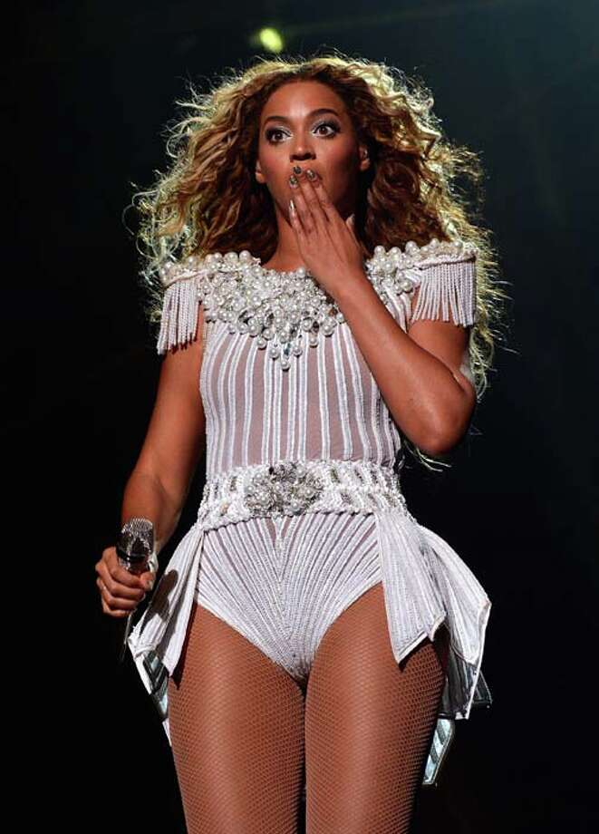 """HOUSTON, TX - JULY 15:  Entertainer Beyonce performs on stage during """"The Mrs. Carter Show World Tour"""" at the Toyota Center on July 15, 2013 in Houston, Texas. Beyonce wears a custom hand beaded white peplum one piece by Ralph & Russo, Stuart Weitzman shoes and hosiery by Capezio.  (Photo by Larry Busacca/PW/WireImage for Parkwood Entertainment) Photo: Larry Busacca/PW, WireImage For Parkwood Entertain / 2013 Larry Busacca/PW"""