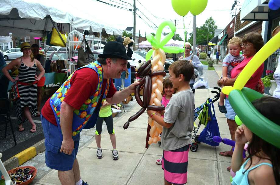 "Greg Vlcek, 10, received an elaborate balloon animal -- a monkey climbing a palm tree -- from ""Mr. Bungles"" of Party Talent at the Darien Sidewalk Sales. Photo: Megan Spicer"
