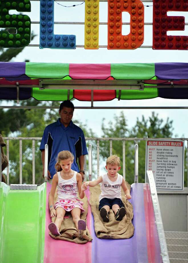 Trinity Aken, left, 9, and Tanner Grabo, 4, both of Ballson Spa, ride the Fun Slide at the Saratoga County Fair in Ballston Spa, NY Tuesday July 16, 2013.  .(John Carl D'Annibale / Times Union) Photo: John Carl D'Annibale / 00023171A