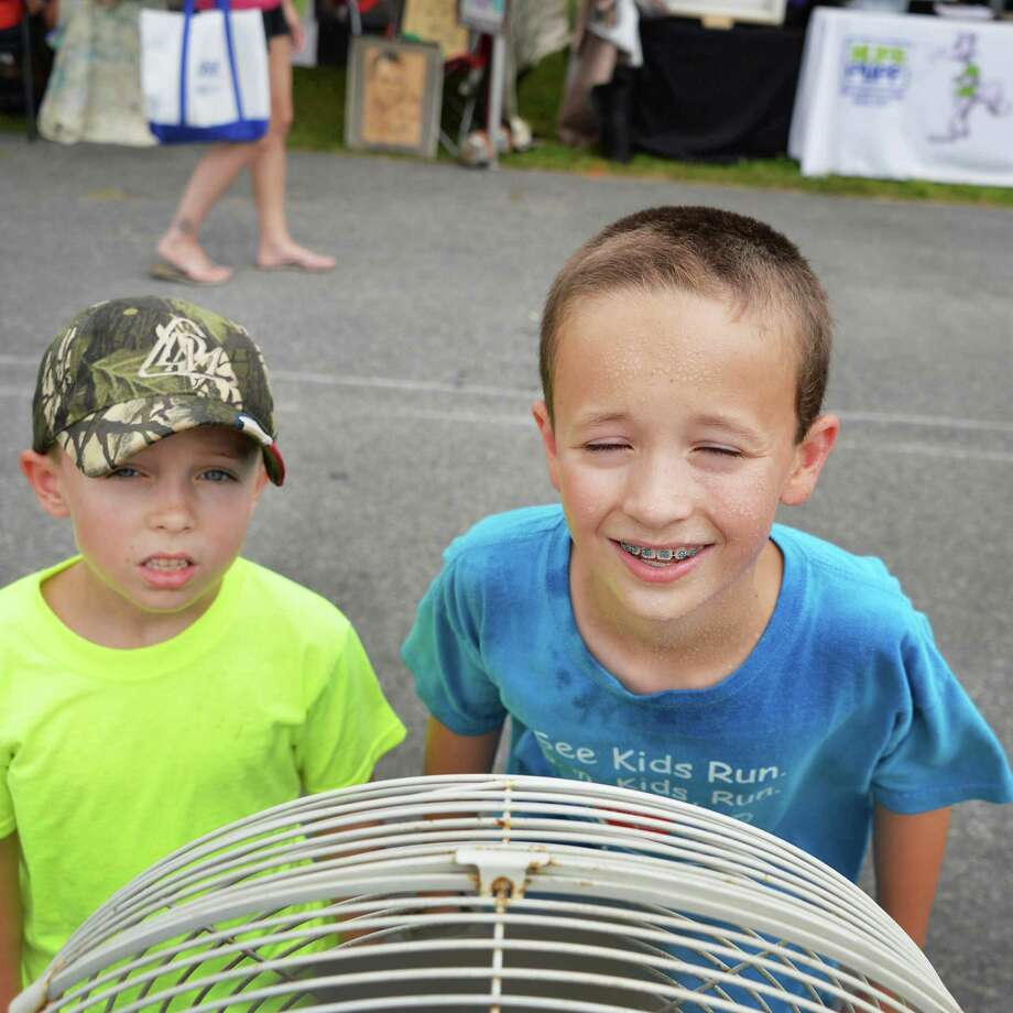"""It's hot, but not as hot as at home,"" says Cameron McCarthy,at right, 10, of Jonesboro, La., as he and brother Ethan, 7, stop at a cooling station Tuesday afternoon, July 16, 2013, at the Saratoga County Fair in Ballston Spa, N.Y. (John Carl D'Annibale / Times Union) Photo: John Carl D'Annibale / 00023171A"