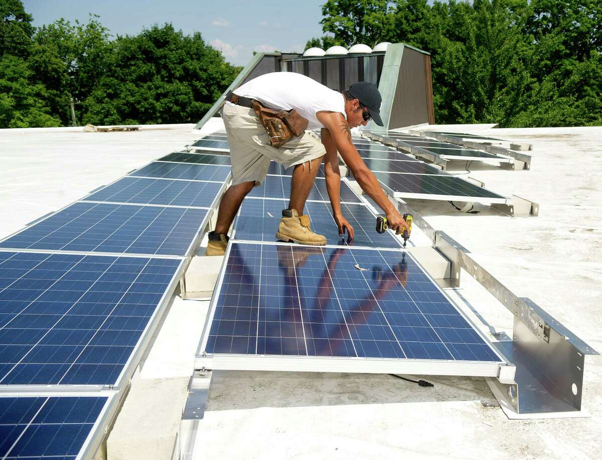 Rafael Souza works installing solar panels on the roof of Temple Beth El in Stamford on Tuesday, July 16, 2013.