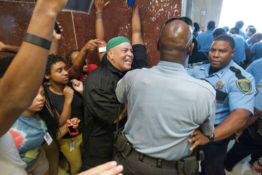 Kofi Taharka with the National Black United Front argues with a police officer after he said the officer pushed protestors out a door in City Hall as more than 100 people protesting broke up the Houston City Council meeting at City Hall in response to George Zimmerman's acquittal in the death of unarmed, black Florida teen Trayvon Martin Tuesday, July 16, 2013, in Houston. 