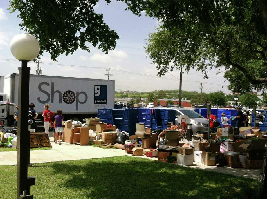 Members and supporters of Texas Children's Choir organize donations that will fill one of eight Goodwill Industries semi trailers. The choir is raising money for a 2014 trip to Normandy, France, where it will participate in the 70th anniversary of the D-Day. Photo: Courtesy Photo