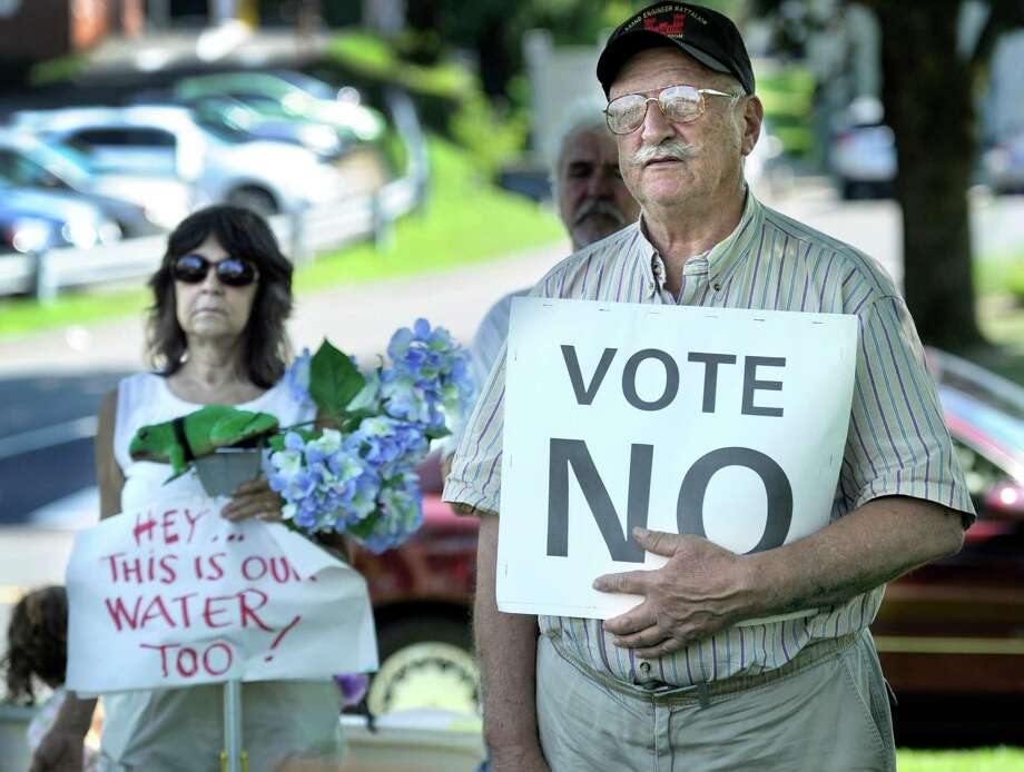 Bethel residents Pam Bujese, left, and John Rondano, participate in a rally protesting the town's proposed sale of the water department to Aquarion Water Company. The rally is held on the grounds on the Bethel Municipal Center, Tuesday, July 16, 2013. Photo: Carol Kaliff / The News-Times