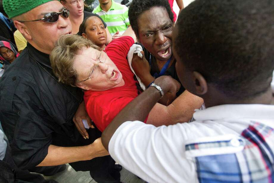 Friends try to calm down, David Wright, top, who reacted after he was told he couldn't enter the Bob Casey Federal Courthouse as more than 100 protestors organized outside the courthouse in response to George Zimmerman's acquittal in the death of unarmed, black Florida teen Trayvon Martin Tuesday, July 16, 2013, in Houston. 