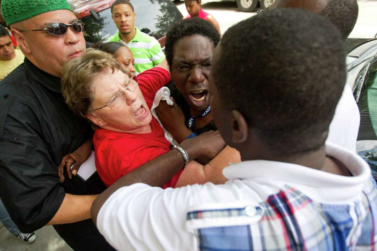 Friends try to calm down, David Wright, top, who reacted after he was told he couldn't enter the Bob Casey Federal Courthouse as more than 100 protestors organized outside the courthouse in response to George Zimmerman's acquittal in the death of unarmed, black Florida teen Trayvon Martin Tuesday, July 16, 2013, in Houston. The group also protested at the city council meeting at City Hall and the Harris County Criminal Justice Center.