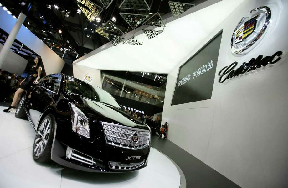 In this Sunday, April 21, 2013 photo, a model poses with a Cadillac XTS displayed at the Shanghai International Automobile Industry Exhibition in Shanghai, China. General Motors' global sales grew almost 4 percent in the first half of the year, enough to fend off Volkswagen to keep second place and perhaps bring the Detroit company closer to sales leader Toyota, according to GM, Tuesday, July 16, 2013. (AP Photo/Eugene Hoshiko) ORG XMIT: NYBZ111 Photo: Eugene Hoshiko / AP
