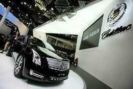 In this Sunday, April 21, 2013 photo, a model poses with a Cadillac XTS displayed at the Shanghai International Automobile Industry Exhibition in Shanghai, China. General Motors?' global sales grew almost 4 percent in the first half of the year, enough to fend off Volkswagen to keep second place and perhaps bring the Detroit company closer to sales leader Toyota, according to GM, Tuesday, July 16, 2013. (AP Photo/Eugene Hoshiko) ORG XMIT: NYBZ111