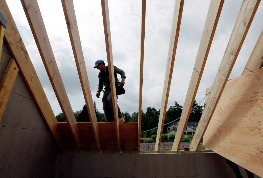 In this Tuesday, July 9, 2013, photo, a worker installs a roof on a zero net energy home on Tuesday, July 9, 2013, in New Paltz, N.Y. The National Association of Home Builders reports on its index of confidence among U.S. homebuilders for July on Tuesday, July 16, 2013. (AP Photo/Mike Groll) ORG XMIT: NYBZ112 Photo: Mike Groll / AP