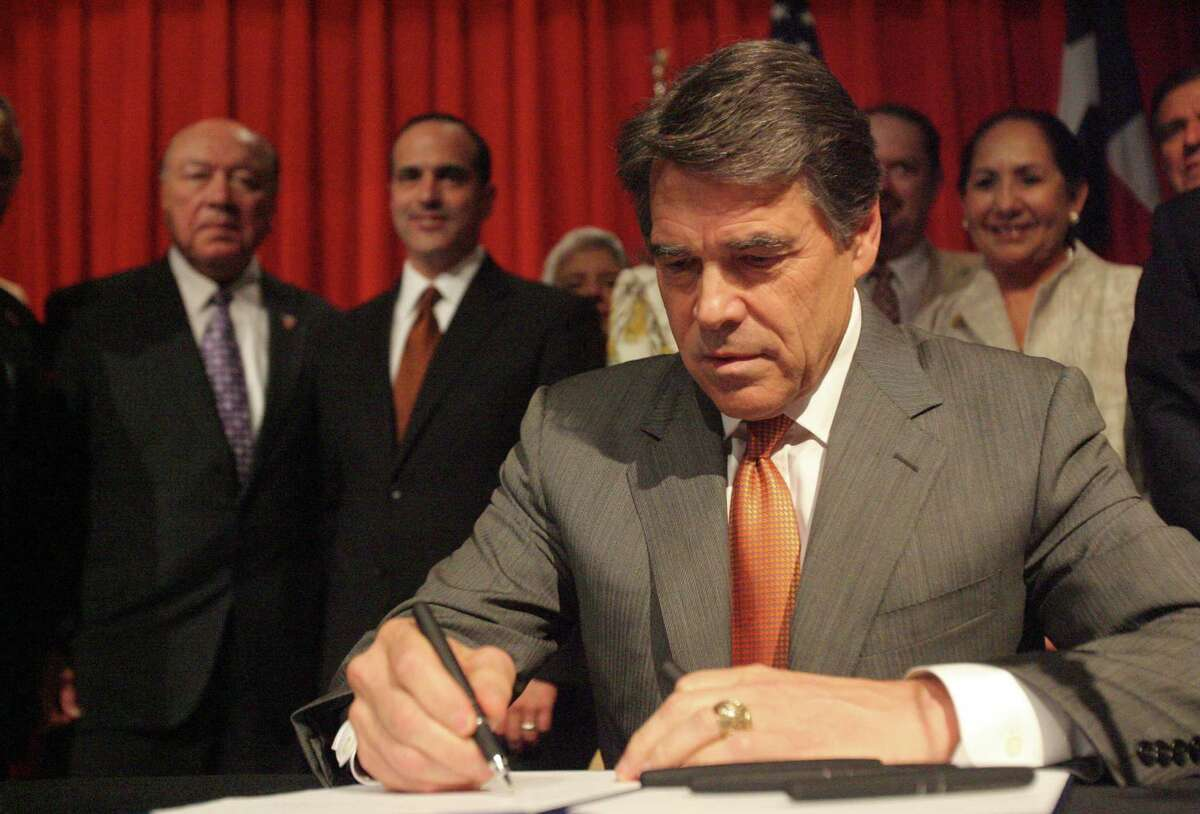 Gov. Rick Perry inks his signiture during the signing of the merger for the new medical school Tuesday July 16, 2013, at the University of Texas Pan American Campus in Edinburg, Texas.