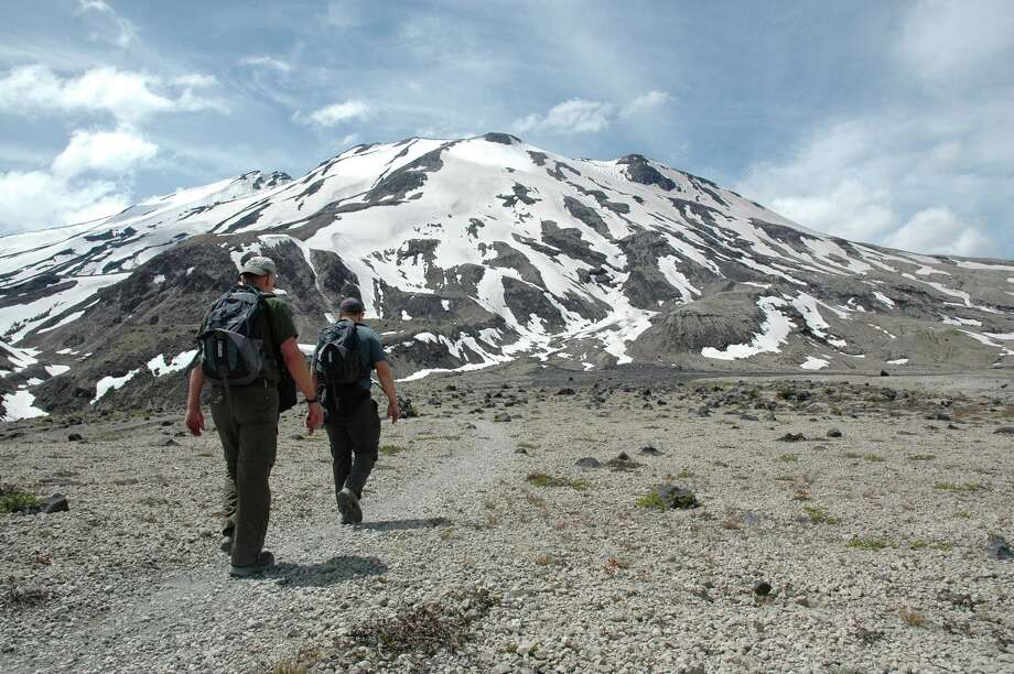 Two hikers cross the Plains of Abraham on the southeast side of Mount St. Helens, Wash. on June 22, 2013.   The hike or ride up Ape Canyon trail is a steady climb.  The elevation is 2,895 feet at the trailhead and 4,202 feet at the junction with Loowit trail No. 216. That's a bit more than 1,300 feet spread out over 4.8 miles, so the grade is not excessive.  Dominating the views are the Muddy River lahar just to the west. Lahar is an Indonesian word for mudflow.  The southeast side of Mount St. Helens has had many lahars over geologic time, including a huge one as part of the massive May 18, 1980 eruption. Photo: The Columbian, Allen Thomas