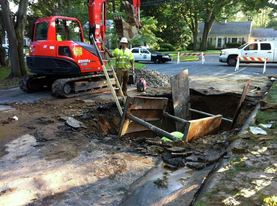 An Aquarion Water Co. crew worked on a 10-foot deep sinkhole on Shea Terrace in Stratford, Conn on Tuesday July 16, 2013.  The sinkhole was caused by a broken water main. Photo: John Burgeson / Connecticut Post