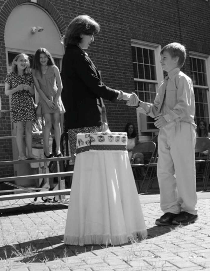 "Principal Trish McGuire shakes 5th grader Christian Cockerill's hand as he prepares to ""ring out"" during last month's tradional ""ringing out"" ceremony at Julian Curtiss School. Photo: Contributed Photo"