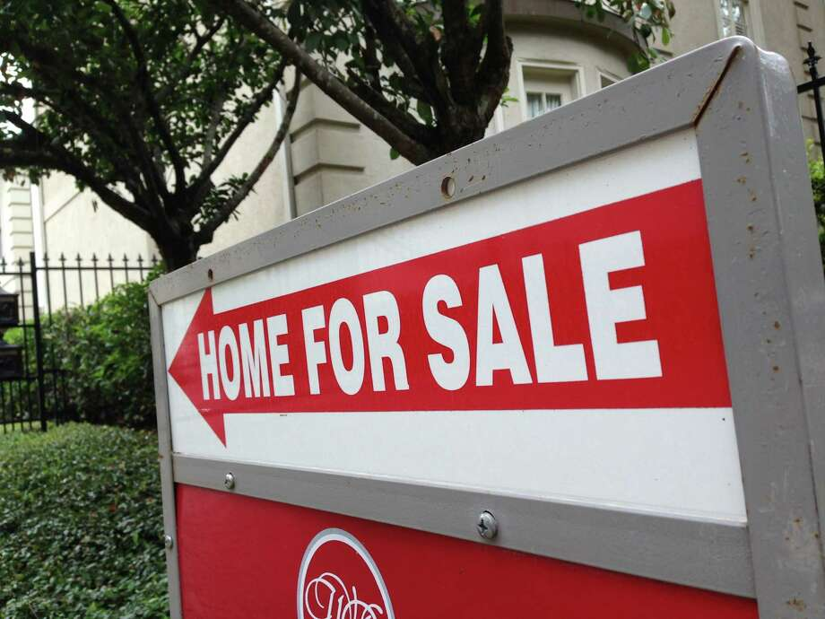 A sign points to a house for sale in the Galleria area of Houston. Homes selling for $250,000 to $1 million and above registered the biggest gains in sales volume in August, the Houston Association of Realtors reported Tuesday. Photo: Katherine Feser