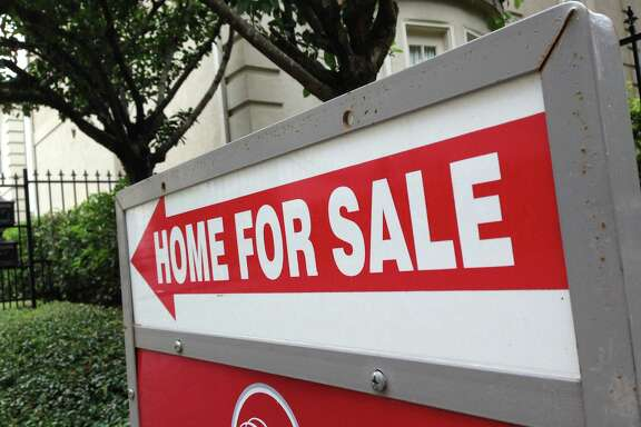 A sign points to a house for sale in the Galleria area of Houston. Homes selling for $250,000 to $1 million and above registered the biggest gains in sales volume in August, the Houston Association of Realtors reported Tuesday.