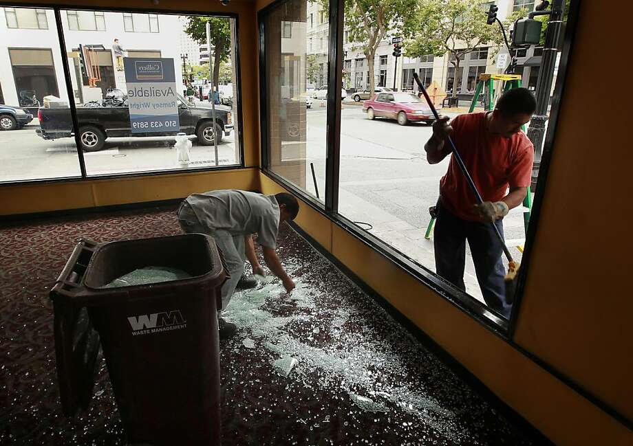 Workers clean up the glass window at a vacant building at 15th Street and Broadway  shattered by protesters. Photo: Michael Macor, San Francisco Chronicle