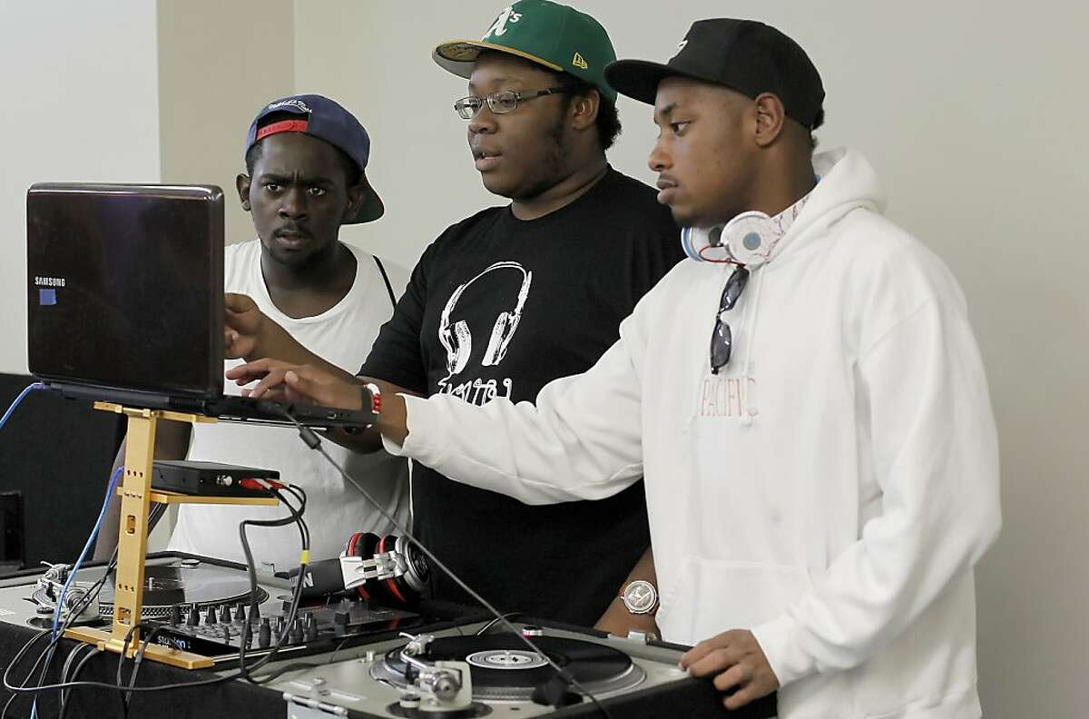Brandon Coles, Nasif Lockett and Sam Mtoto work together during the DJ program at the non-profit Youth Radio in Oakland, Calif on Tuesday July 16, 201. Their building had several broken windows after a third night of protests following the acquittal of George Zimmerman in the Trayvon Martin killing in Florida.