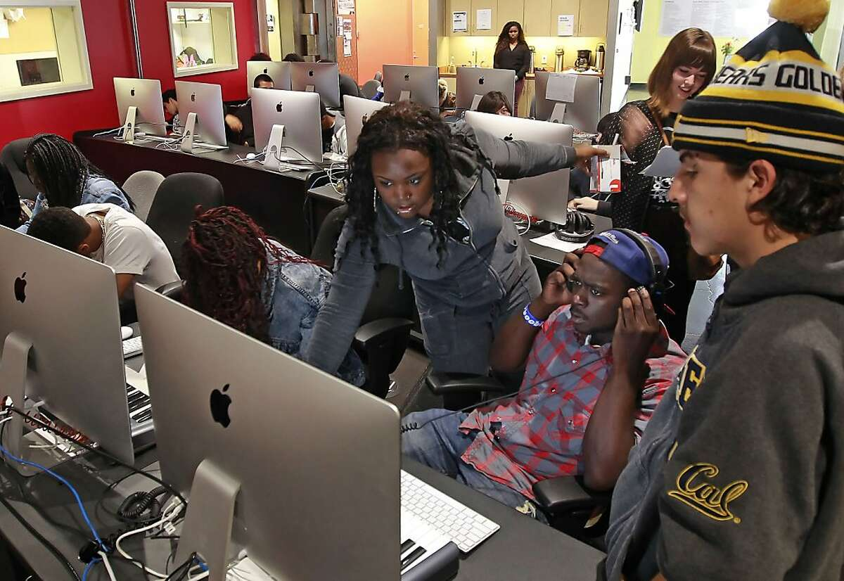 Project associate Joi Morgan assists new students, Brandon Coles, (center) and Tino Becerra in music production at the non-profit Youth Radio in Oakland, Calif on Tuesday July 16, 2013. Their building had several broken windows after a third night of protests following the acquittal of George Zimmerman in the Trayvon Martin killing in Florida.