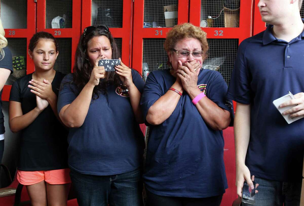 Sabina Bebee holds back tears as the Houston Texans' Whitney Mercilus, Jon Weeks, and QB TJ Yates present a jersey plaque in honor of her son, fallen firefighter Robert Bebee, during the Houston Texans surprise visit to Houston Fire Station No. 51 to show their appreciation and support for the men and women of the Houston Fire Department on Tuesday, July 16, 2013, in Houston.