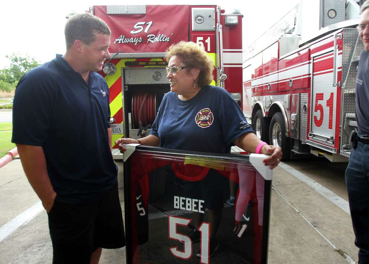 Houston Texans Jon Weeks chats with Sabina Bebee who holds a plaque in honor of her son and fallen firefighter Robert Bebee during a surprise visit to Houston Fire Station No. 51 to show their appreciation and support for the men and women of the Houston Fire Department on Tuesday, July 16, 2013, in Houston.