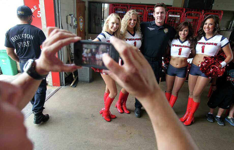 Firefighter Christopher Dorsett poses for a photo with the Houston Texans during a surprise visit to Houston Fire Station No. 51 to show their appreciation and support for the men and women of the Houston Fire Department on Tuesday, July 16, 2013, in Houston. Photo: Mayra Beltran / © 2013 Houston Chronicle