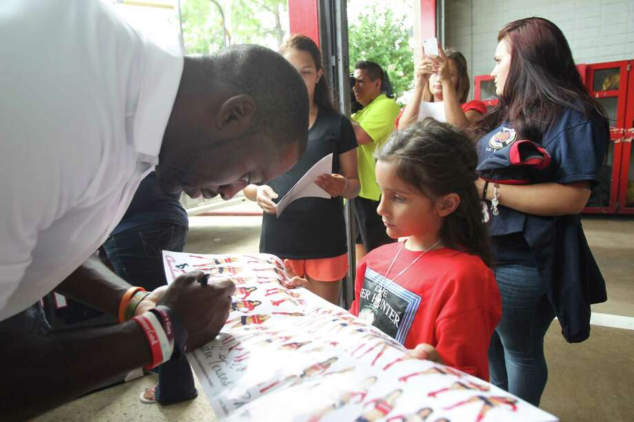 Houston Texans Whitney Mercilus sings an autograph for Justice Garcia, niece of fallen firefighter Robert Bebee, during a surprise visit to Houston Fire Station No. 51 to show their appreciation and support for the men and women of the Houston Fire Department on Tuesday, July 16, 2013, in Houston. Photo: Mayra Beltran / © 2013 Houston Chronicle