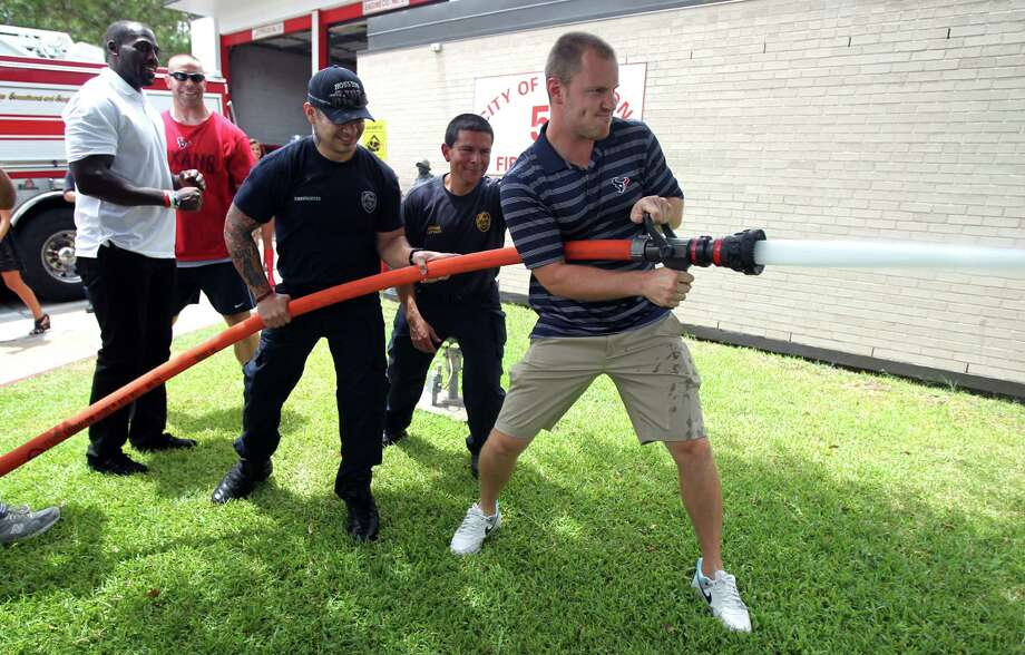 Houston Texans T.J. Yates turns on a water hose during a surprise visit to Houston Fire Station No. 51 where firefighters gave them a tour of firehouse and show equipment on Tuesday, July 16, 2013, in Houston. Photo: Mayra Beltran / © 2013 Houston Chronicle