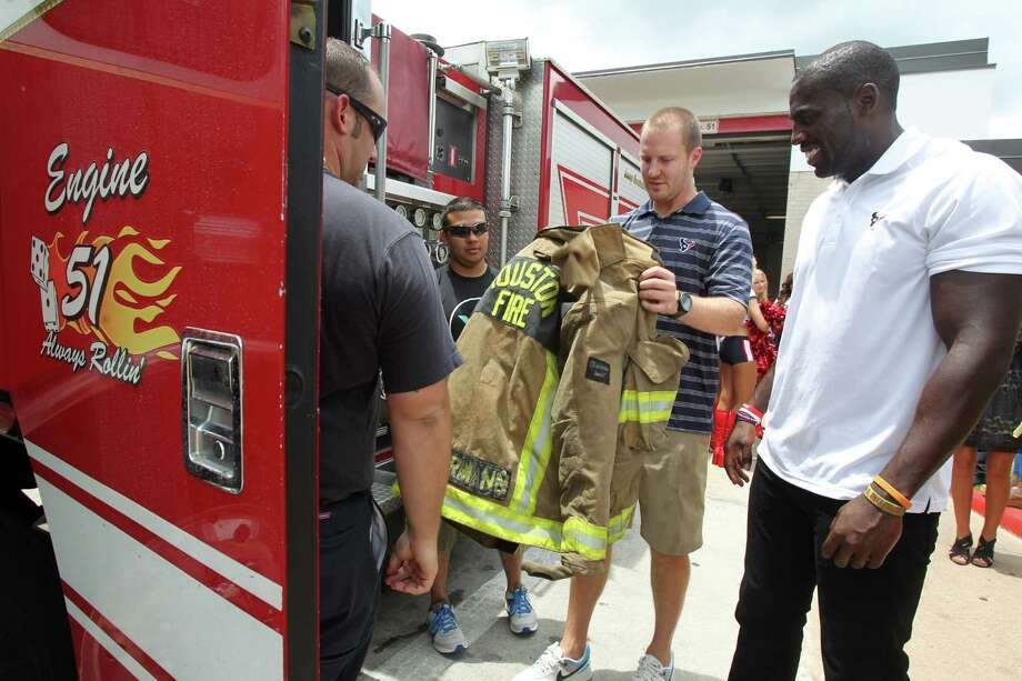 Houston Texans T.J. Yates and Whitney Mercilus learn how heavy protective clothing is during a surprise visit to Houston Fire Station No. 51 where firefighters give them a tour of firehouse on Tuesday, July 16, 2013, in Houston. Photo: Mayra Beltran / © 2013 Houston Chronicle