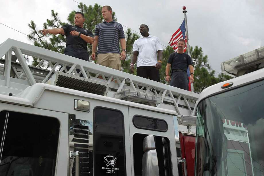 Firefighter Frank Cervantes and Ken Coursey show Houston Texans T.J. Yates and Whitney Mercilus how to operate the ladder during a surprise visit to Houston Fire Station No. 51 where firefighters gave them a tour of firehouse on Tuesday, July 16, 2013, in Houston. Photo: Mayra Beltran / © 2013 Houston Chronicle