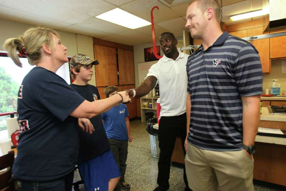 Jacki Dowling, wife of Capt. William Dowling, shakes hands with Houston Texans Whitney Mercilus, and QB T.J. Yates during a visit to Houston Fire Station No. 68 to show their appreciation and support for the men and women of the Houston Fire Department on Tuesday, July 16, 2013, in Houston. Photo: Mayra Beltran / © 2013 Houston Chronicle