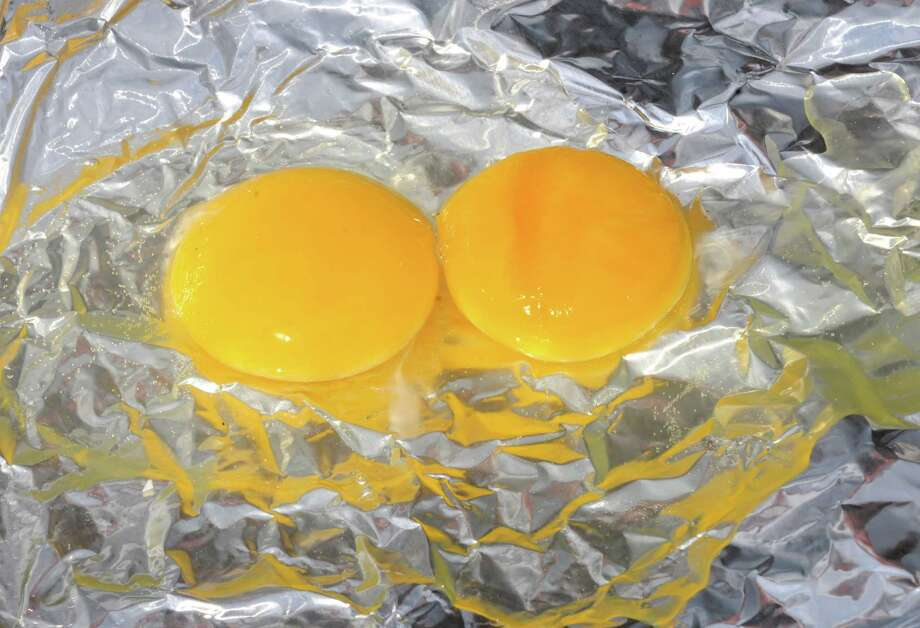An experiment to see if it was hot enough to cook an egg on the tarmac at Albany International Airport on Tuesday afternoon, July 16, 2013, in Colonie, N.Y.  (Michael P. Farrell/Times Union) Photo: Michael P. Farrell / 00023189A