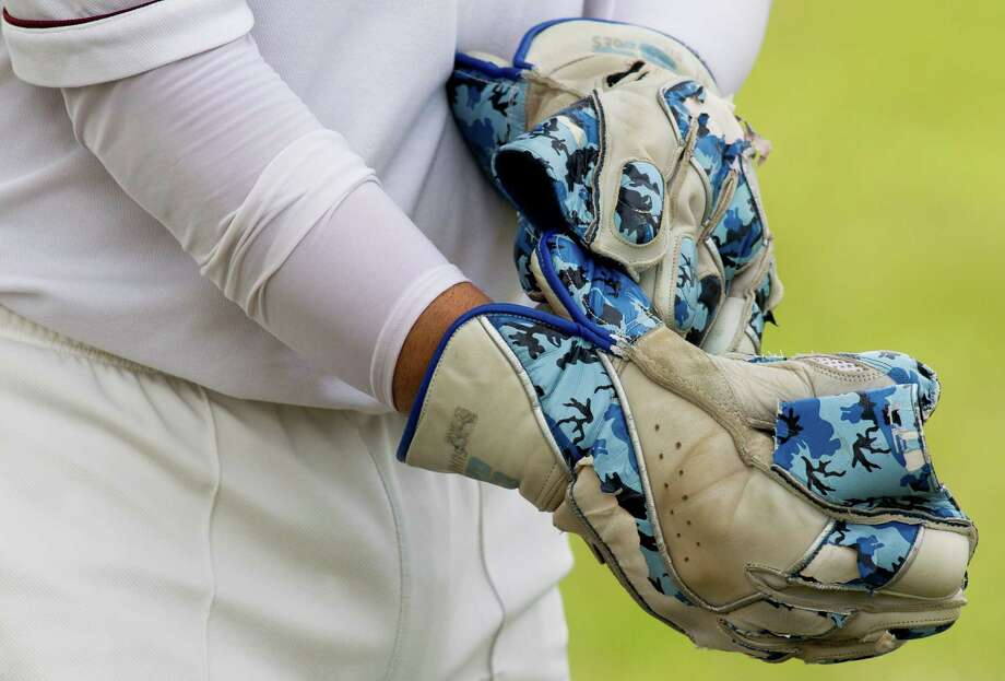 Houston Indian Cricket Club wicket-keeper Monik Patel puts on his wicket keeping gloves before a cricket match at George Bush Park on Sunday, June 30, 2013, in Houston. The wicket-keeper is much like a catcher in baseball standing directly behind the batsman. Photo: J. Patric Schneider, For The Chronicle / © 2013 Houston Chronicle