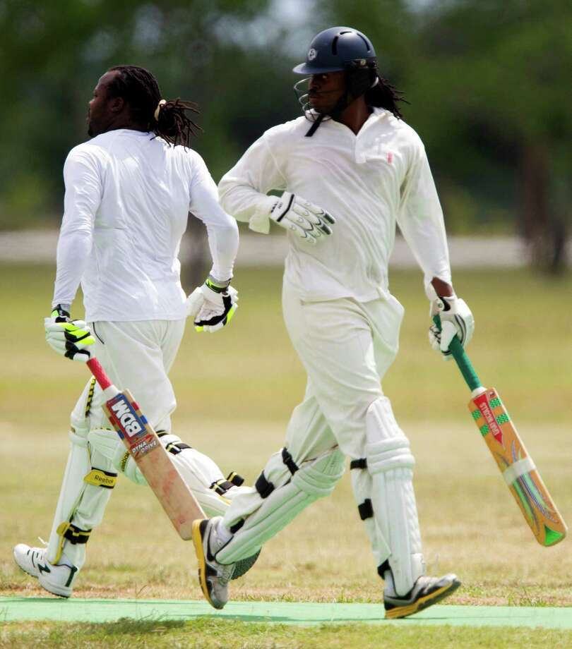 Houston West Indies batsman Henry Nelson, left, and Demar Bethune cross as they run to score by touching a wicket (a small post) during a cricket match against the Houston Indian Cricket Club at George Bush Park on Sunday, June 30, 2013, in Houston. Photo: J. Patric Schneider, For The Chronicle / © 2013 Houston Chronicle