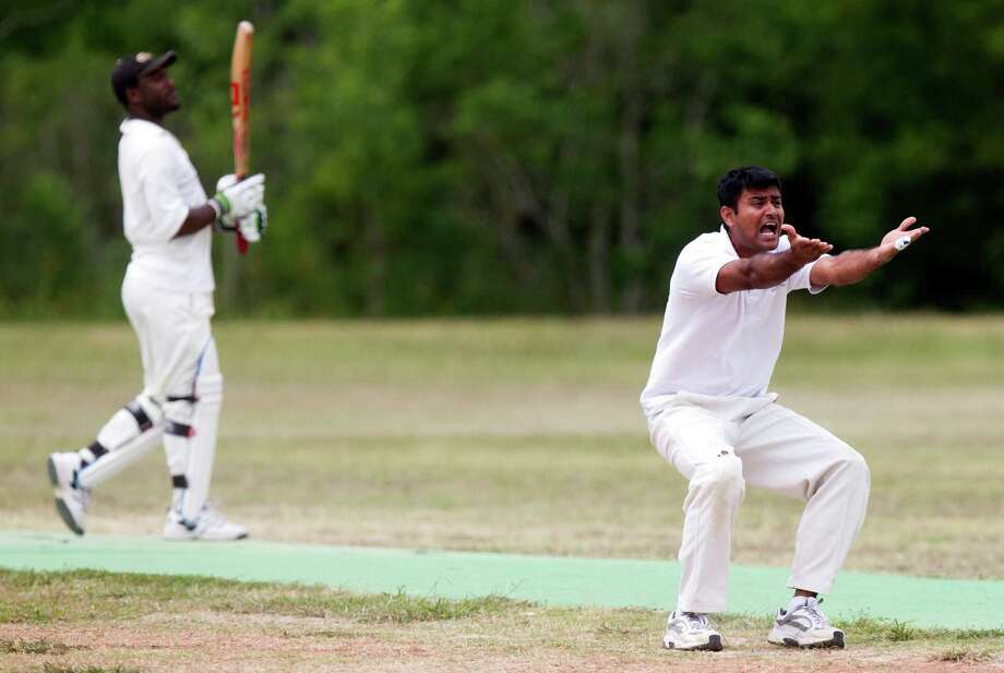 Houston Indian Cricket Club bowler Kalpesh Patel argues a call as Houston West Indies batsman Travis Wynter looks on during a cricket match at George Bush Park on Sunday, June 30, 2013, in Houston. Photo: J. Patric Schneider, For The Chronicle / © 2013 Houston Chronicle