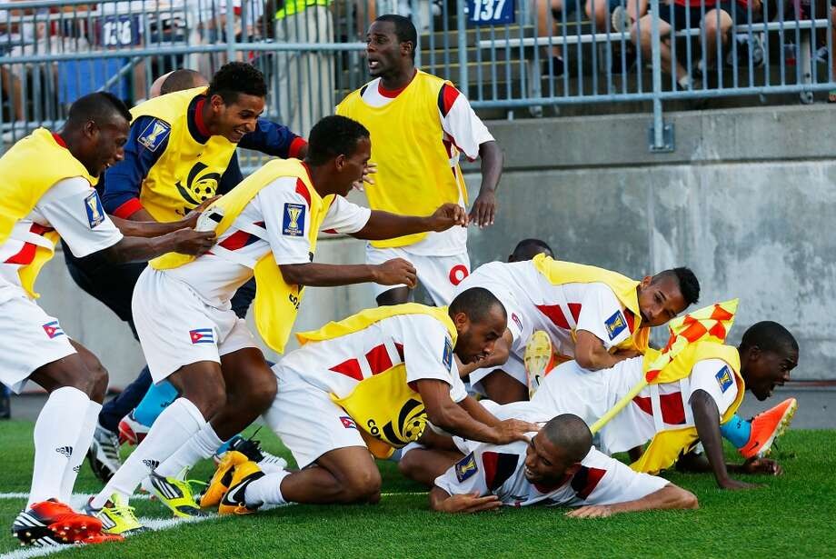 HARTFORD, CT - JULY 16: Jeniel Molina #3 of Cuba is mobbed by his teammates after scoring a goal in the 90th minute against Belize during the CONCACAF Gold Cup match at Rentschler Field on July 16, 2013 in East Hartford, Connecticut. (Photo by Jared Wickerham/Getty Images)