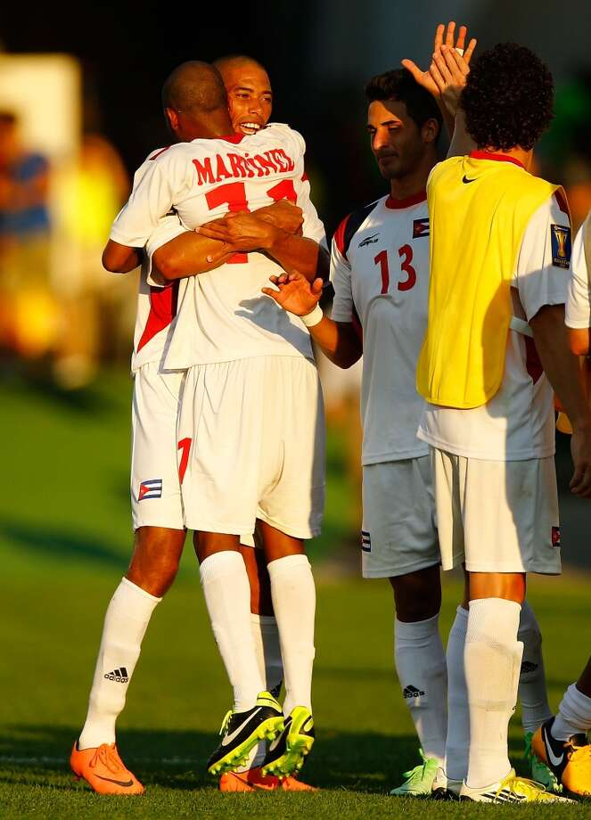 HARTFORD, CT - JULY 16: Jeniel Molina #3 of Cuba is celebrates with teammate Ariel Pedro Martinez #11 of Cuba after scoring a goal in the 90th minute against Belize during the CONCACAF Gold Cup match at Rentschler Field on July 16, 2013 in East Hartford, Connecticut. (Photo by Jared Wickerham/Getty Images)