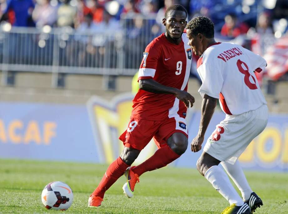 Belize's Deon McCauley, left, eyes a pass while being guarded by Cuba's Jaine Valencia during the second half of a CONCACAF Gold Cup soccer match Tuesday, July 16, 2013, in East Hartford, Conn. Cuba won 4-0. (AP Photo/Fred Beckham)