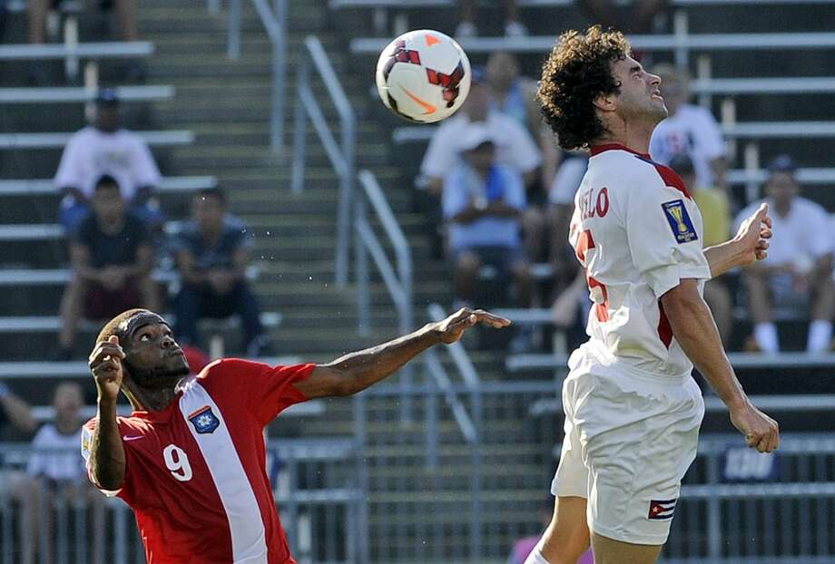 Cuba's Jorge Luis Clavelo, right, fights for a loose ball with Belize's Deon McCaulay during the first half of a CONCACAF Gold Cup soccer match Tuesday, July 16, 2013, in East Hartford, Conn. (AP Photo/Fred Beckham)