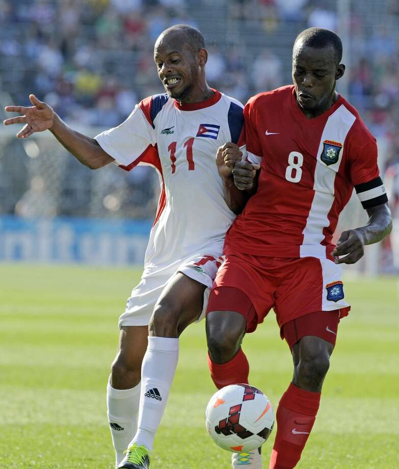 Cuba's Ariel Pedro Martizez, left, fights for a loose ball with Belize's Elroy Smith during the first half of a CONCACAF Gold Cup soccer match Tuesday, July 16, 2013, in East Hartford, Conn. (AP Photo/Fred Beckham)