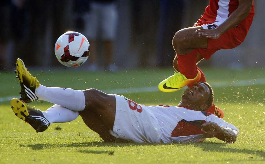 Cuba's Jaine Valencia, bottom, attempts to tackle Belize's Luis Torres during the second half of a CONCACAF Gold Cup soccer match Tuesday, July 16, 2013, in East Hartford, Conn. Cuba won 4-0. (AP Photo/Fred Beckham)