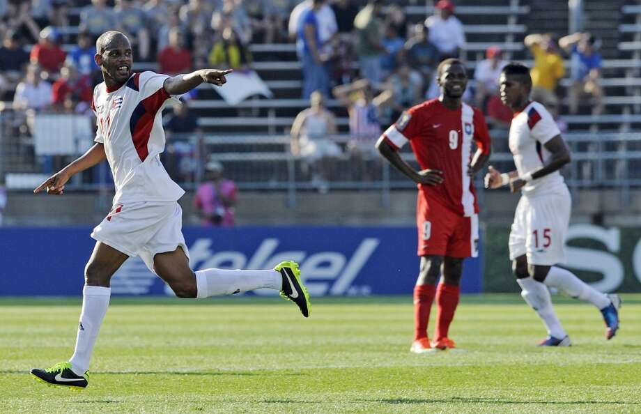 Cuba's Ariel Pedro Martinez, left, celebrates after scoring a goal during the first half of a CONCACAF Gold Cup soccer match against Belize Tuesday, July 16, 2013, in East Hartford, Conn. (AP Photo/Fred Beckham)