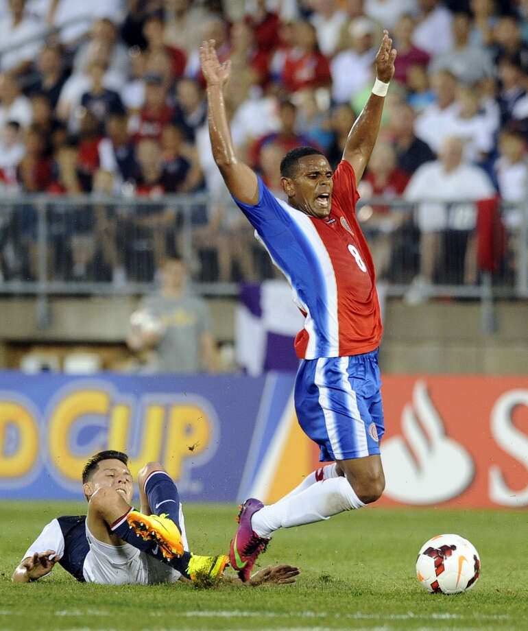United States' Jose Torres falls after challenging Costa Rica's Kenny Cunningham during the first half of a CONCACAF Gold Cup soccer match Tuesday, July 16, 2013, in East Hartford, Conn. (AP Photo/Fred Beckham)