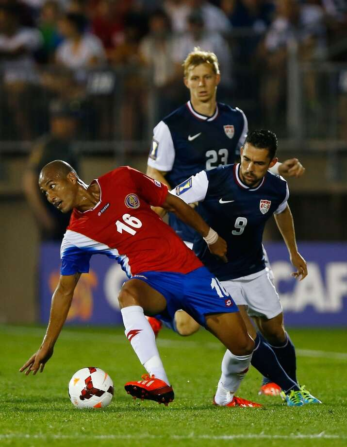 HARTFORD, CT - JULY 16: Carlos Johnson #16 of Costa Rica carries the ball in front of Herculez Gomez #9 of the United States during the CONCACAF Gold Cup match at Rentschler Field on July 16, 2013 in East Hartford, Connecticut. (Photo by Jared Wickerham/Getty Images)