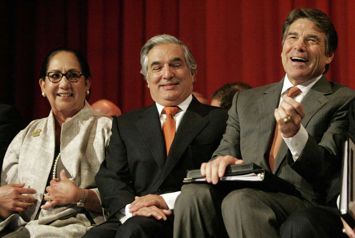 University of Texas at Brownsville President Juliet V. Garcia (left), University of Texas Chancellor Francisco Cigarroa and Gov. Rick Perry share a laugh in 2013 before Perry signed the bill for the merger for the new medical school at the University of Texas-Pan American in Edinburg.