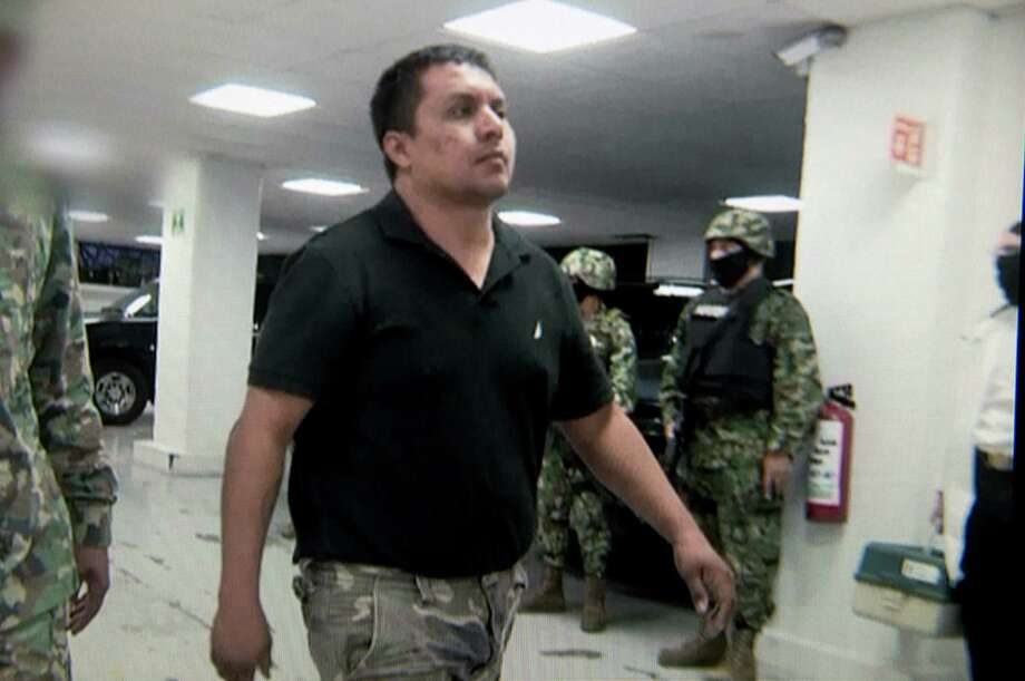 CALM IMAGE: An unshackled Miguel Treviño Morales,                  the Zetas leader arrested Monday, is seen striding along a hallway after being taken in. Photo: Mexican Navy / Getty Images