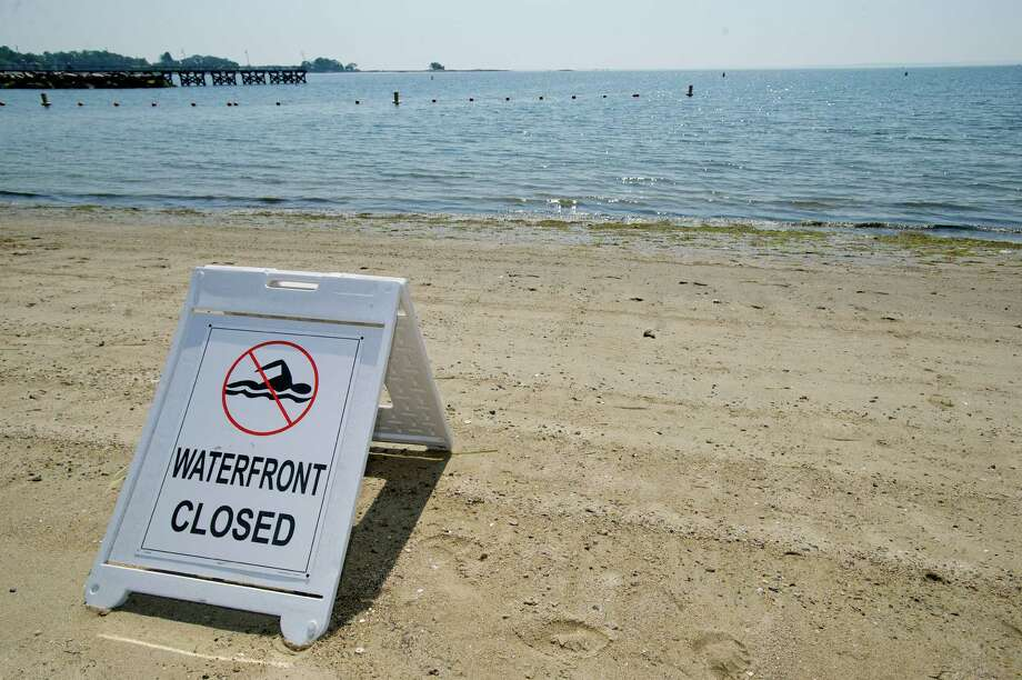 A sign notifying swimmers that the water is closed sits on West Beach in Stamford, Conn., on Wednesday, July  17, 2013. Photo: Lindsay Perry / Stamford Advocate