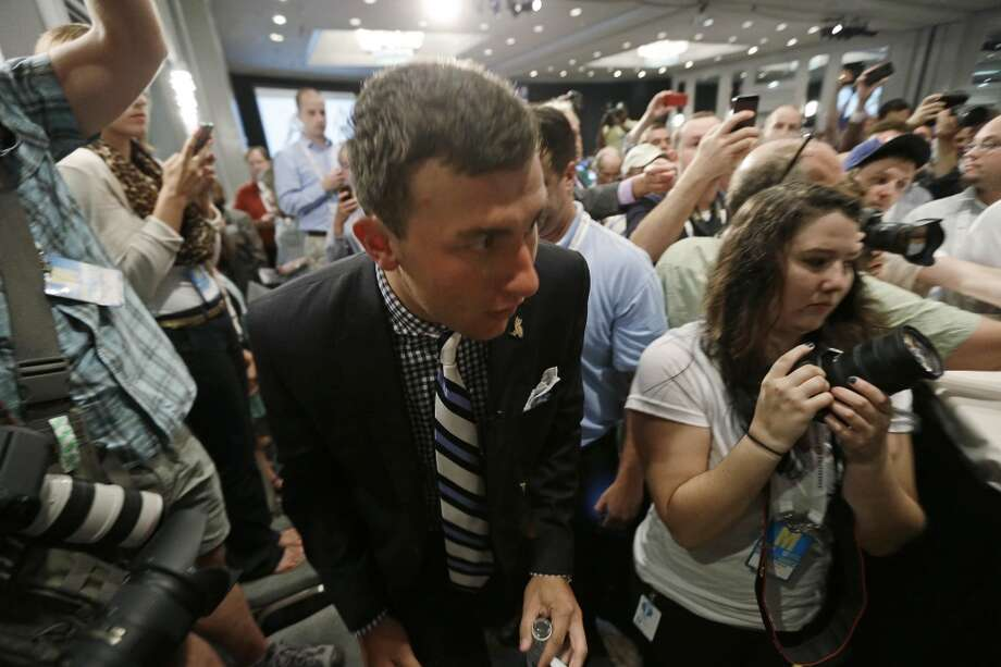 Texas A&M quarterback Johnny Manziel fights his way through a crowd of photographers and reporters as he arrives for the SEC media days on Wednesday in Hoover, Ala.