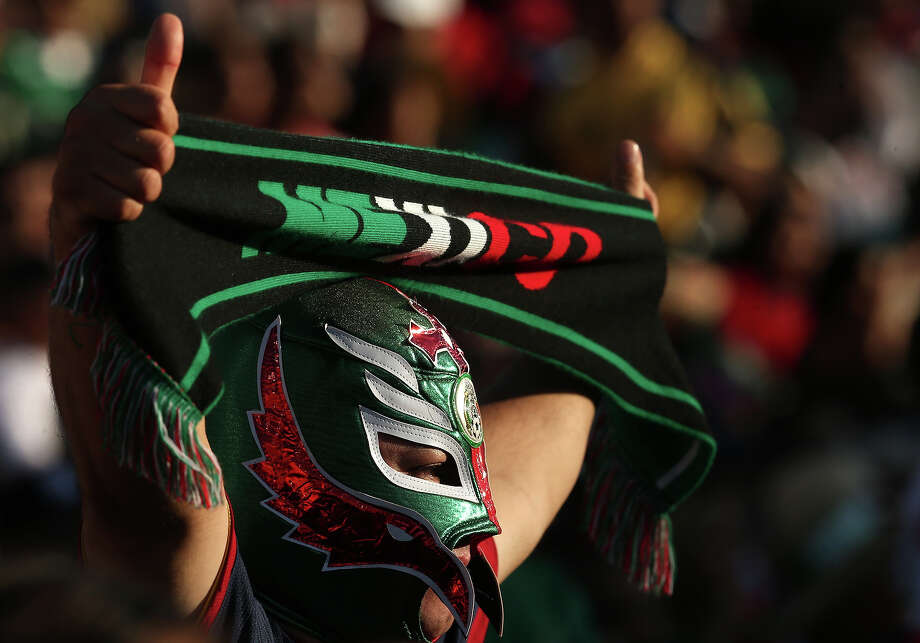 A  Mexico fan wearing a luche libre mask holds up a scarf in the game with Panama during the first round of the 2013 CONCACAF Gold Cup at the Rose Bowl on July 7, 2013 in Pasadena, California. Panama won 2-1. Photo: Stephen Dunn, Getty Images / 2013 Getty Images